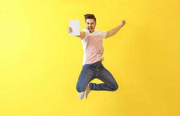 Jumping young man with book on color background Wall mural