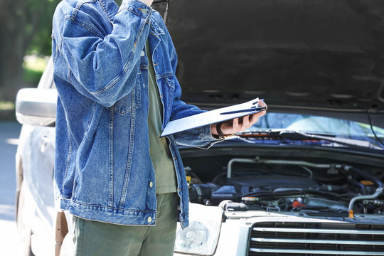 Insurance agent inspecting car after accident