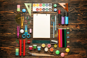 Different school stationery on wooden background