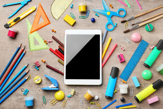 Different school stationery and tablet computer on wooden background