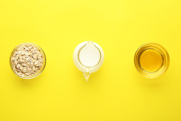 Bowls with oat flakes, honey and milk in jug on color background