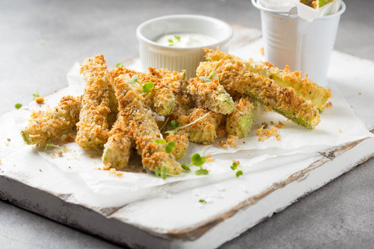 Zucchini sticks in breadcrumbs, with cheese, herbs, breadcrumbs and white yogurt sauce. Healthy snack, summer food