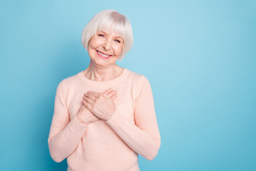 Portrait of positive woman putting her palm on chest smiling wearing pastel sweater isolated over blue background