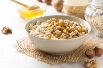 Oatmeal with nuts (hazelnuts, walnuts) and honey, porridge for Breakfast. Tasty, healthy food