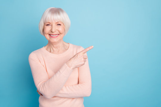 Portrait of lovely lady pointing at copy space having toothy smile isolated over blue background