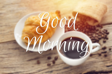 text good morning with blurry of continental breakfast with fresh croissant and hot coffee on wooden table, decoration with coffee bean as background