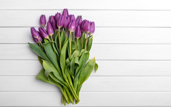Bouquet of tulips on white background of the wooden planks.