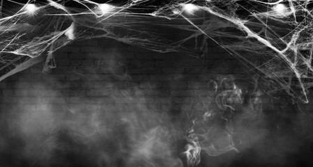 Halloween background. Background of old brick wall, cobweb, smoke, concrete floor