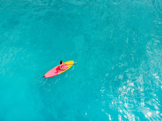 Aerial view of woman on stand up paddle board in blue ocean.