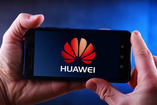 Hands holding smartphone displaying logo of Huawei