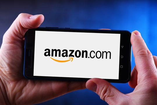 Hands holding smartphone displaying logo of Amazon