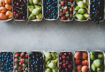 Summer fruit and berry variety. Flat-lay of ripe strawberries, cherries, grapes, blueberries, pears, apricots, figs in wooden eco-friendly boxes over grey background, top view, copy space Fototapete
