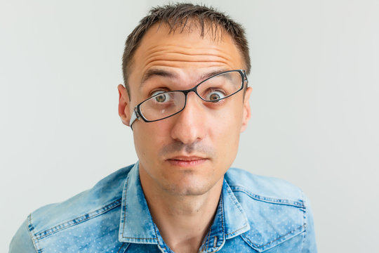 Closeup portrait of frustrated, mad angry nerdy young man with big glasses, screaming fists raised, isolated on white background. Negative emotions facial expressions feelings, body language