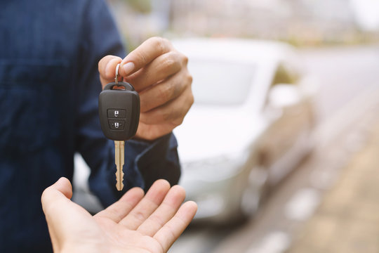 Car key, businessman handing over gives the car key to the other woman on car background.