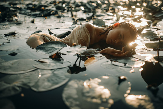 Young woman lying in the water among the leaves and flowers of yellow water-lily.