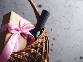 A bottle of red wine and a gift box with a bow in a basket with copyspace