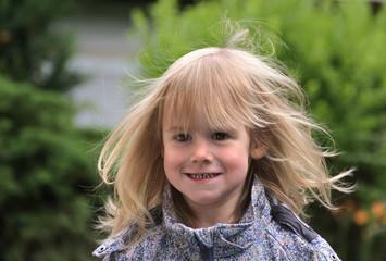 Portrait kleines blondes Mädchen mit fliegenden Haaren