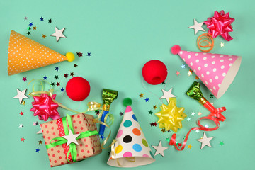 Birthday caps,  present, confetti, ribbons,  stars,  clown noses on a green background. Space for text or design.