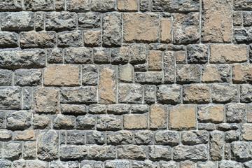 Alte grau braune Steinmauer aus groben, herausstehenden Natursteinen im Sonnenschein