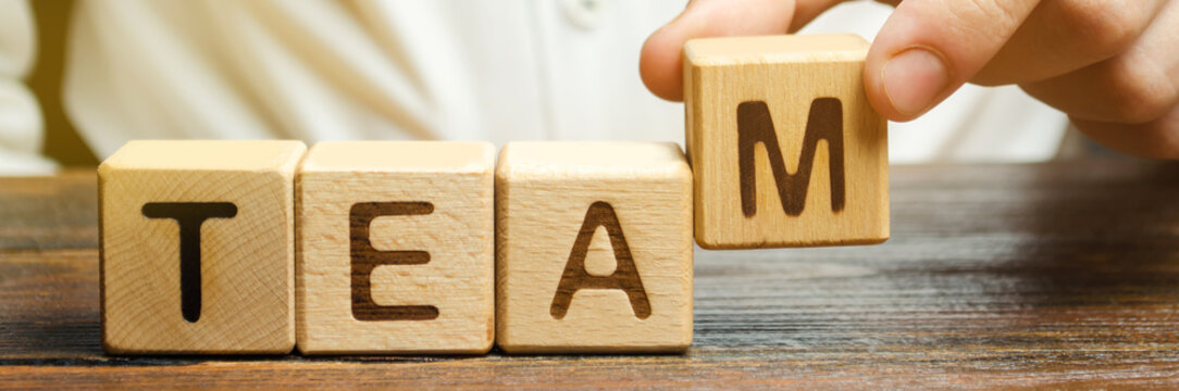 Businessman holds wooden blocks with the word Team. Team management concept. Teamwork. Hiring. Recruitment staff. Work in cooperation. Leadership skills. Analysis and analytics business process