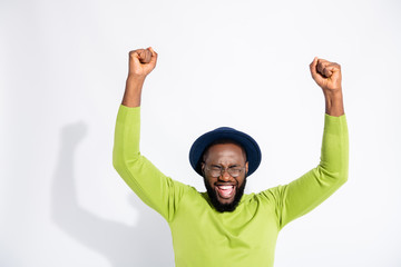 Portrait of ecstatic man with closed eyes screaming shouting yeah wearing green sweater isolated over white background