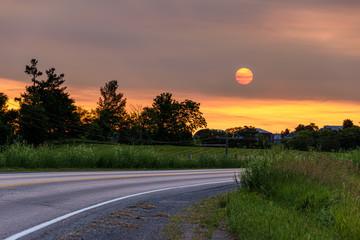 orange sunrise on curved road