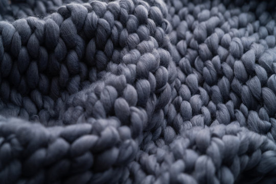 Merino wool handmade knitted large blanket, super chunky yarn, trendy concept. Close-up of knitted blanket, merino wool background. designer blanket made of beige smoky wool.