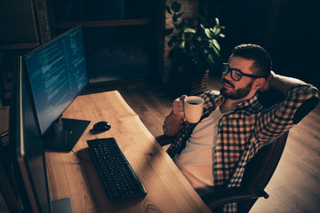 Close up photo handsome enjoy mug hot beverage he him his guy relaxing big chair coder php css development outsource IT processing two monitors table office agency wear specs formalwear shirt