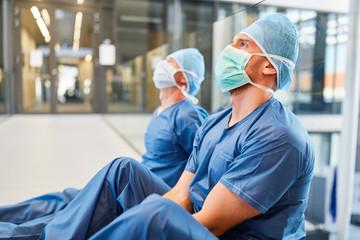 Zwei erschöpfte Chirurgen in blauer OP-Kleidung Wall mural