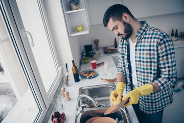 Profile side view of his he nice attractive focused hard-working guy wearing checked shirt doing domestic rub scrubbing plates in modern light white interior style kitchen indoors