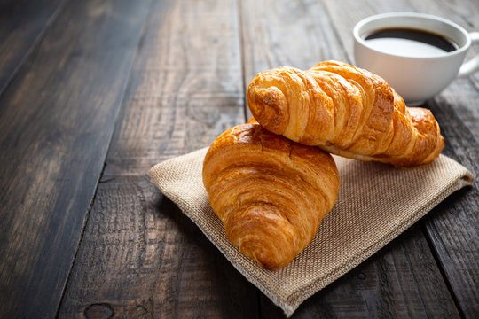 croissants and coffee on old wooden table.