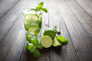 Mojito drink with lime, lemon and mint on wooden table.