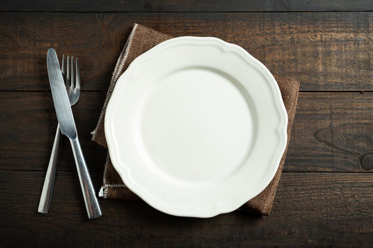 Empty white plate on wooden table.