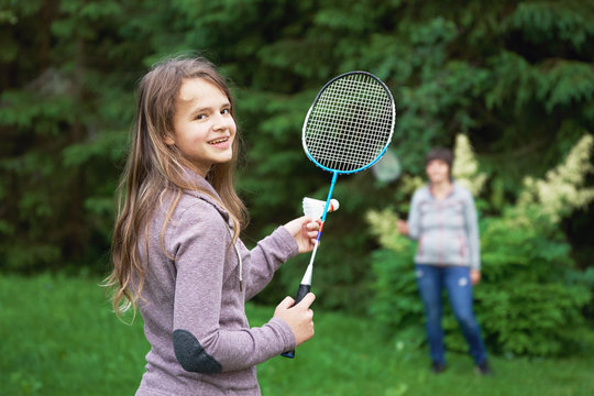 Smiling teenage girl playing badminton with her mother outdoors