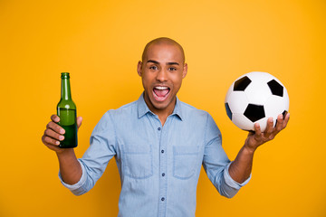 Photo of dark skin guy hold hand beer bottle ball sport bar support favorite team wear jeans denim shirt isolated bright yellow background