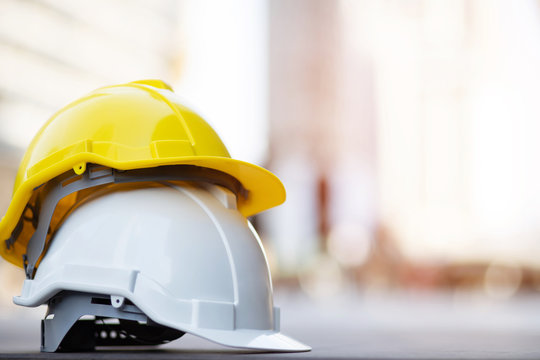 yellow and white hard safety wear helmet hat in the project at construction site building on concrete floor on city with sunlight. helmet for workman as engineer or worker. concept safety first.