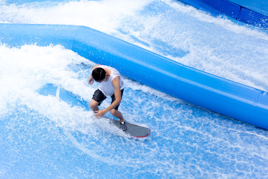 unidentified man playing surfboard indoor extreme sport.