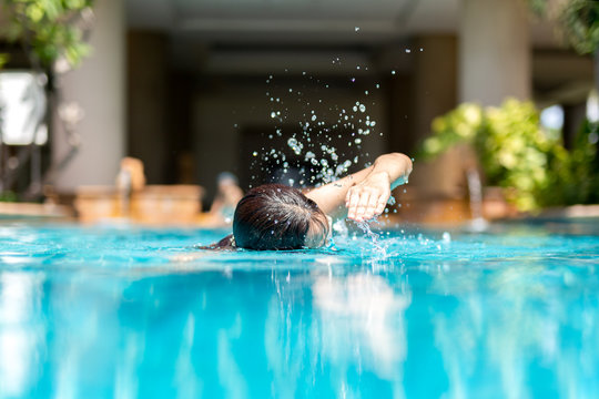 Unidentified woman doing front crawl swimming in swimming pool on vacation.