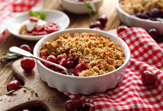 Cherry crumble in a baking dish on a wooden table, close-up