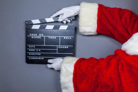 Weihnachtsmann hält Filmklappe in Hand