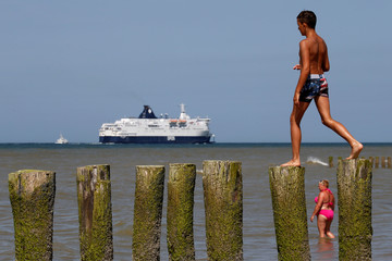 People cool off in the sea on a hot summer day as a ferry sails past the beach in Sangatte