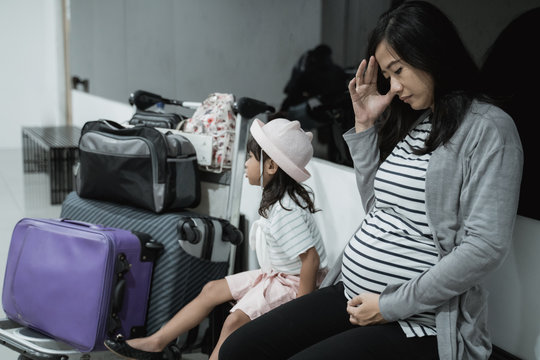 pregnant asian woman feel dizzy and his daughter when in the waiting room airport before flight departure