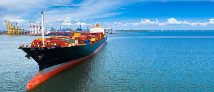 Aerial view container cargo ship carrying commercial container in import export business commerce logistic and transportation of international by container ship boat with copy space for banner web.
