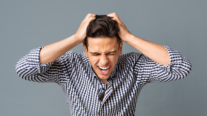 Frustrated Young Man Pulling His Hair Out On Gray Background
