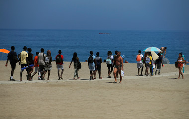 People arrive at La Malagueta beach, as the summer's second heatwave hits Spain, in Malaga