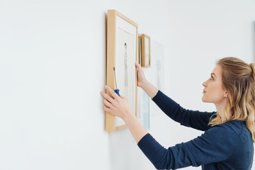 Young woman hanging a picture on a wall