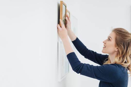 Young woman decorating her home hanging pictures
