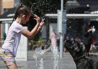 A girl plays with her dog in a water fountain on a hot summer day in Brussels