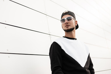 Nice urban young hipster man in stylish sweatshirt in black trendy black baseball cap in sunglasses in the city. Handsome guy model poses near the white wall. New youth collection of men's clothing. Wall mural