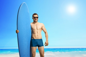 Young handsome man with a surfboard at a beach